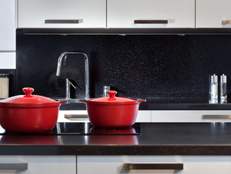 Kitchen with white cabinets, black countertop and backsplash, and red pots on the stove.