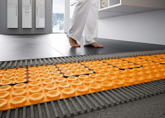 Feet on a tiled bathroom floor with a cutaway revealing the orange Ditra Heat mat and cable underneath.