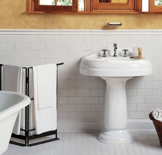 "Bathroom with white pedestal sink, white octagon-and-dot mosaic tile floor, 3x6"" white subway tile wainscoting topped with a white ceramic chair rail. The walls are painted with a yellow faux finish."