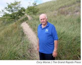 Lester Langeland, of the Ottawa Conservation District, stands on Dewey Hill in Grand Haven. Trees and dune grass were planted on the hill in 1941 by the conservation district to stop erosion.