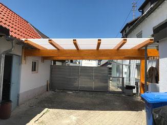 Terrassenüberdachung in Balingen aus Brettschichtholz mit Plexiglas Wellplatten Heatstop Cool blue als Dacheindeckung. Auf der Linken Seite haben wir ein Auflager in der Mauer des bestehenden Schuppens geschaffen.Anstrich mit Holzlasur Kiefer.