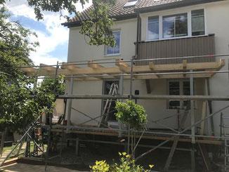 Terrassenüberdachung in Balingen Endingen. Auf den Dachsparren werden Glasplatten montiert.