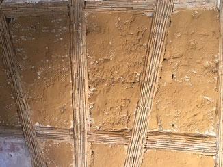 Vorbereitung Fachwerk für Lehmputz. Gefache mit Lehmschlämme vorgestrichen. Schilfrohr Putzträger auf Fachwerkbalken montiert.