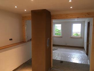 Beim Ausbau in Balingen haben wir die Lehm verputzten Wände mit weißer Lehmfarbe gestrichen. Der Kamin wurde Lehmsichtig belassen. Auf dem Foto ist der Lehm am Kamin noch feucht daher die dunkelbraune Farbe.