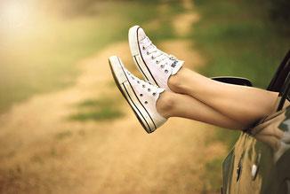 Entspannte Füße in Turnschuhen hängen aus Autotür