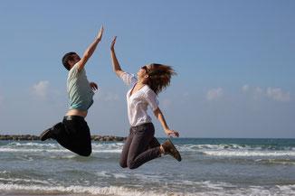 Mann und Frau springen in die Höhe, klatschen sich gegenseitig ab