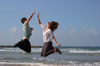 Mann und Frau springen in die Luft und klatschen sich an den Händen