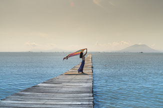 Frau auf Steg im Meer lässt buntes Tuch im Wind flattern