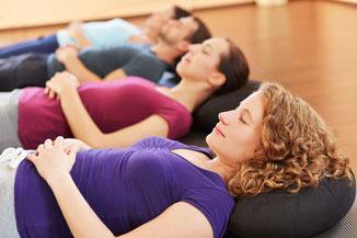 Mehrere Personen entspannt auf Matten liegend in einem Entspannungskurs
