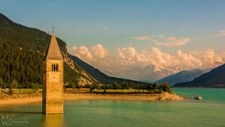 Der berühmte Kirchturm von Graun, im Hintergrund die schneebedeckten Gipfel der Ortler-Alpen