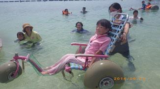 水に浮く車いすに乗って笑顔の障害当事者