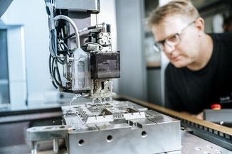 Mitarbeiter arbeitet an einer Fräsmaschine.