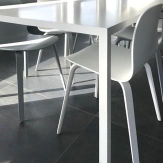 Tisch und Stuhl Kombination in weiss und grau. Formensprache welche zum Unternehmen passt.