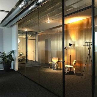 Emotional und stilvoll gestaltete Interiors/ Räume steigern jeden Wert. Sicht durch eine Glasabtrennung auf Designermöbel von Vitra, Baltensweiler und Atelier Pfister  stehen vor einer goldenen Wellblech Wand.
