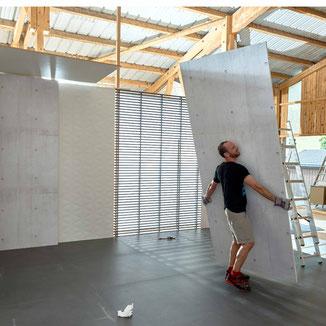 Kulissenbau in einer alten Halle. Philipp Brunschwiler trägt eine Bauwand. Badezimmer Making Of