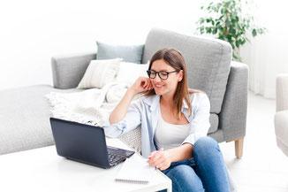 Frau sitzt auf dem Boden in ihrem Wohnzimmer vor dem Laptop und befindet sich in einem online Coaching