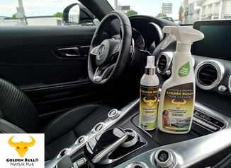 Autoleder effizient reinigen und pflegen mit dem vierteiligen Lederpflege-Set von Golden Bull. Auf dem Bild sind die Produkte Foam Cleaner und Intensive Care stehend im Cockpit des Mercedes Benz AMG GT zu sehen.