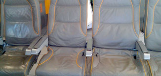 Grey aircraft seats treated with Golden Bull Readymix cleaner and care for leather. Aircraft interior cleaning and care agent Golden Bull Readymix for avitation industry.