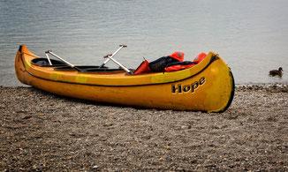 Kanadier am Strand mit Schwimmwesten und Paddel