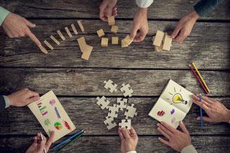 verschiedene Hände auf einem Holztisch, jeder hat eigene Vorschläge diese werden auf den Tisch gelegt.