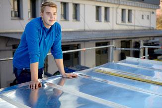 Stellenangebote. Mitarbeiter vor einem Blechdach
