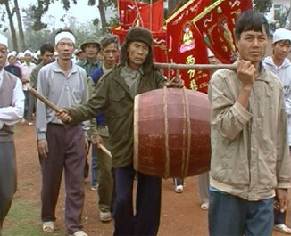 Funeral procession. The later carrier himself hits the barrel drum. Vietnam.