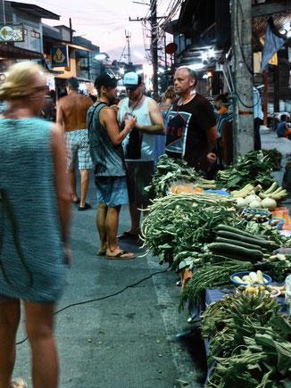 Frau steht vor Gemüse auf einem thailändischen Markt