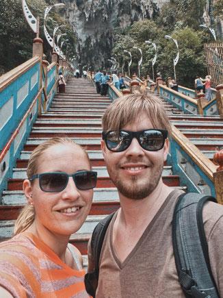 Pärchen steht auf den Stufen zur Batu Cave in Kuala Lumpur.