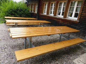 3 grosse Tische mit Bänken vor dem Haus