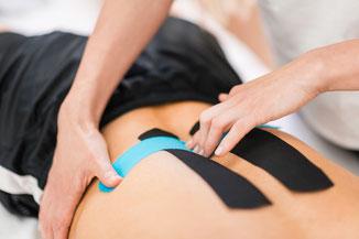 Kinesiotape wird durch Therapeuten auf Rücken angebracht