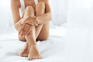 Auf Boden sitzende Frau umfasst ihre enthaarten Beine