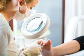 Zehennägel werden durch Fußpflegerin beschnitten