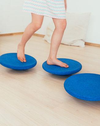 Kind balanciert auf Stapelstein BALANCE BOARD blue basic
