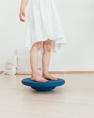 Kind balanciert auf einem Stapelstein BALANCE BOARD nightblue