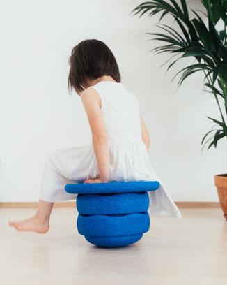 Kind sitzt auf Stapelsteinen