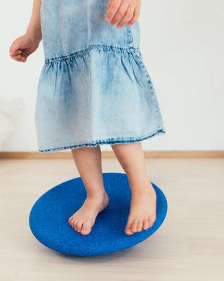 Kind balanciert auf Stapelstein BALANCE BOARD blue