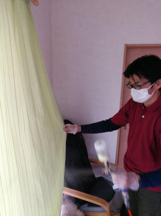 室内カーテンに光触媒をコーティングしている様子。光触媒には抗菌だけでなく防臭効果もあります。-PicaService(ピカサービス)