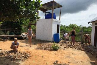 volunteers help cleaning the building site