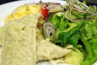 Maultaschen neben grünem Salat und Karatoffelsalat mit Zwiebeln