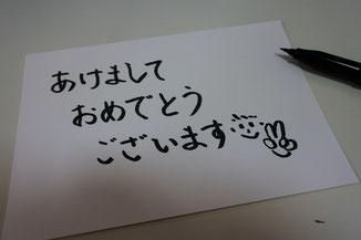 まずは筆ペンで白い紙に手書き文字をしたためて…