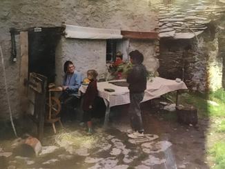 Annett am Spinnrad, im Gespräch mit einem Kind. Historische Aufnahme aus dem Familienalbum.