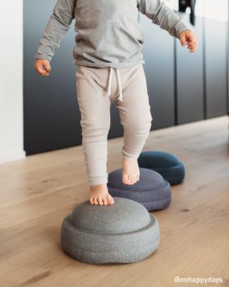 Kind balanciert auf Stapelsteinen