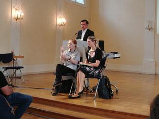 Das Foto zeigt Herrn Scheder am Rednerpult. Davor sitzen 2 Gebärdensprach-Dolmetscherinnen.