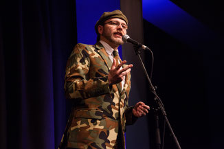 Moderation auf höchstem Niveau mit schrillen Outfits: Michael Jakob (Zirndorf) leitet den Neumarkter Poetry Slam. Fotograf: Valentin Olpp