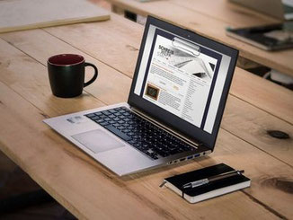 Foto eines Laptops am Tisch mit Kaffee und Notizbuch