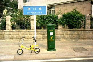 mein gelbes Mini-Bike neben der grünen Postbox-Säule