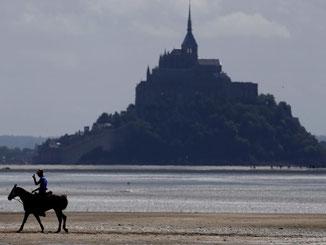 Am Mont-Saint-Michel in Frankreich rüsten sich Einheimische und Touristen für eine sogenannte Jahrhundert-Flut. Foto: Ian Langsdon
