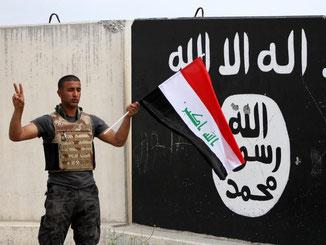 Ein irakischer Soldat in Tikrit steht mit seiner Landesflagge vor einer Wand mit dem Emblem der Terrororganisation IS. Foto: Baraa Kanaan, Archiv