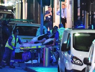 Rettungskräfte holen Verletzte aus dem von der Polizei gestürmten Café. Foto: Mick Tsikas