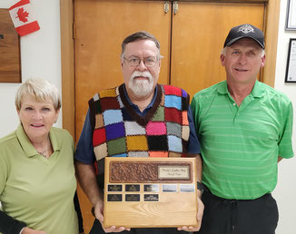 Photo of tournament winners MaryLou Demers and Dave Austen with sponsor Martin Henly and tournament trophy.